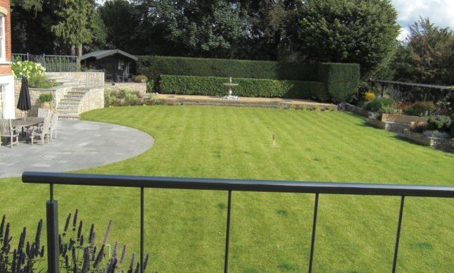 A sloping garden design in Kenley, Surrey, with stone walls, stainless steel rainings, and terraced levels.