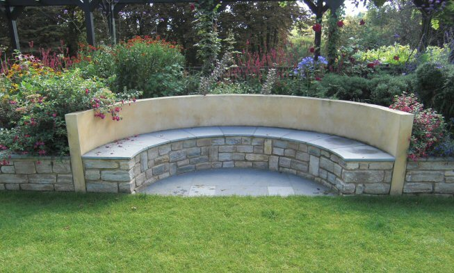 A built-in bench in a sloping garden design in Kenley, Surrey, with stone walls, stainless steel rainings, and terraced levels.