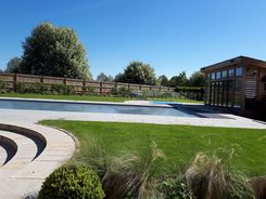 Garden design in Denham, Buckinghamshire with raised swimming pool terrace and curved steps.