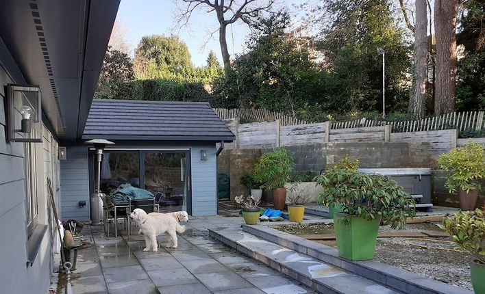 A sloping garden design in Hindhead, Surrey, with retaining walls, an outdoor kitchen, a waterfeature, built-in seating, and terraced levels.