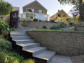 Garden design in Bracknell, Berkshire with feature wall, raised beds, sunken seating area and raised beds.