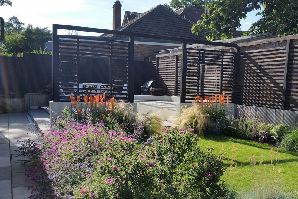 Garden design in Crowthorne, Berkshire with outdoor rooms, fireplace, pergola and terraced levels.