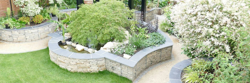 Garden design in St Albans, Hertfordshire with gabion retaining walls and a steel pergola.
