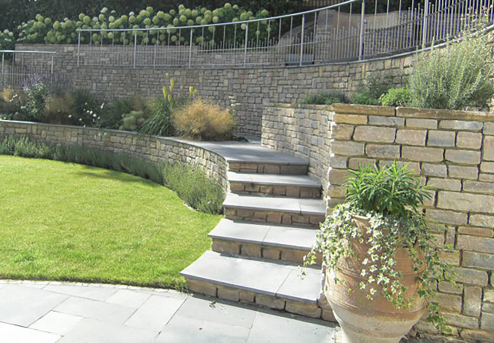 A sloping garden design in Kenley, Surrey, with stone walls, stainless steel rainings, and terraced levels. .
